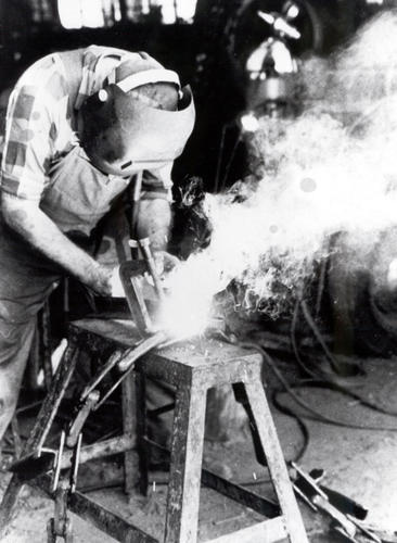 black and white photo of man welding