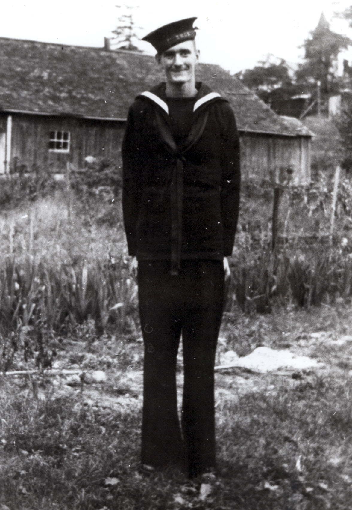 Byard Donnelly stands in his World War two naval uniform in front of a wood plank home.