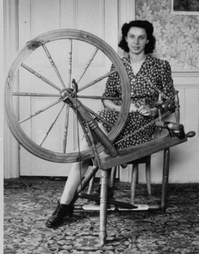 woman sits at spinning wheel