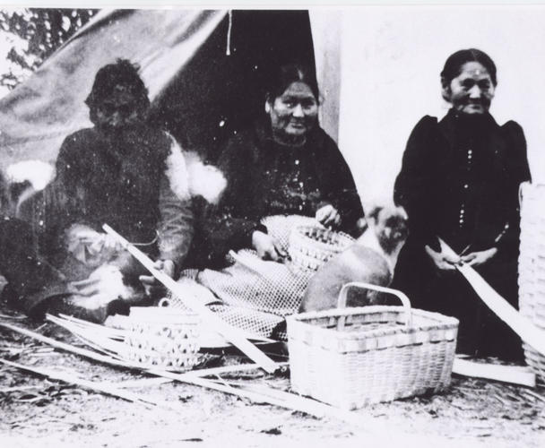 First Nations women seated n the ground with baskets in front of them