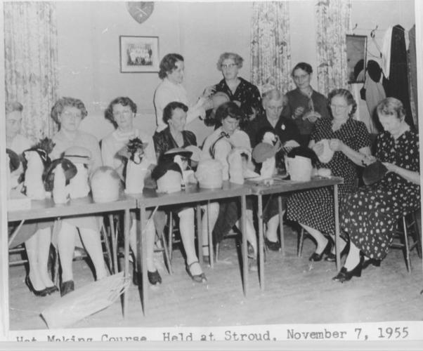 women seated at table with hat making supplies in front of them