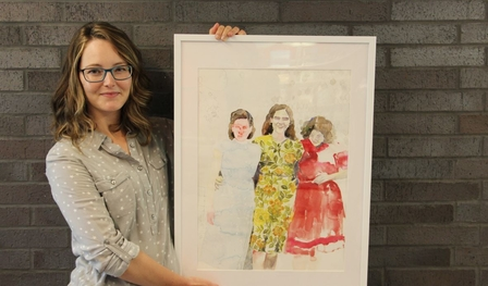 Artist Jacqueline Swanek holds one of her framed watercolour paintings