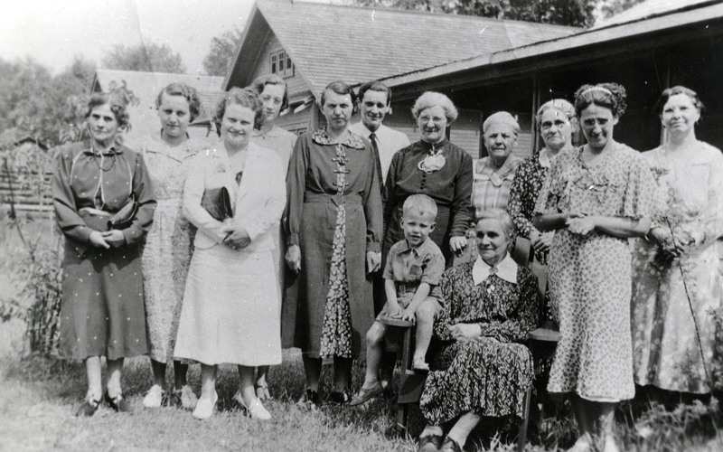 A group of women standing and seated for a photo outdoors in 1934